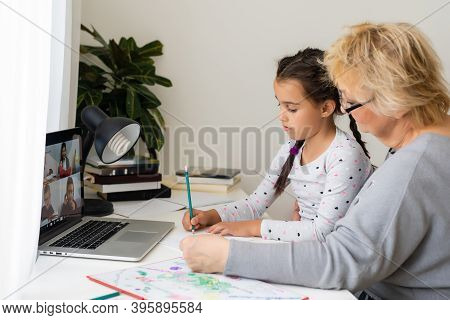 Mature Grandmother Helping Child With Homework At Home. Satisfied Old Grandma Helping Her Granddaugh