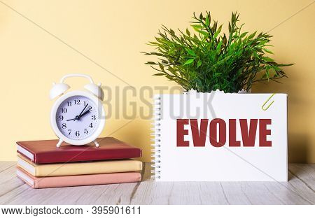Evolve Is Written In A Notebook Next To A Green Plant And A White Alarm Clock, Which Stands On Color