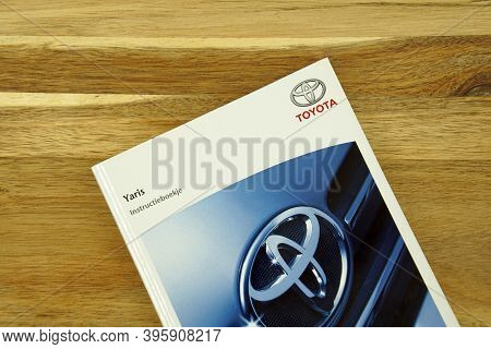 Amsterdam, The Netherlands - November 22, 2020: Toyota Yaris Owner's Manual On A Wooden Table.