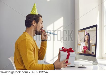 Happy Young Man Sitting At Computer And Having Virtual Party With His Friend Or Girlfriend
