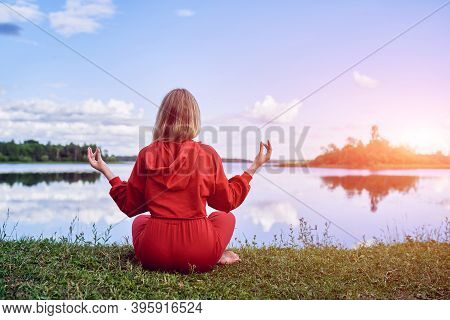 A Girl In A Red Suit Is Sitting Back In A Lotus Position On The Shore Of A Lake And Meditating. Cont