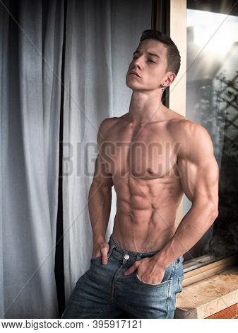 Muscular Topless Young Man Standing Between Drapes