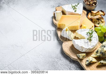 Assorted Cheeses On A Wooden Cutting Board. Camembert, Brie, Parmesan And Blue Cheese With Grapes An