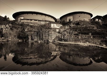 FUJIAN, CHINA – MARCH 2, 2018: Chuxi Tulou Cluster with water reflection. Tulou is the unique traditional rural dwelling of Hakka.