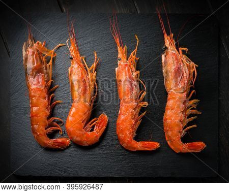 Four Large Langoustines On A Black Plate. Seafood Healthy.