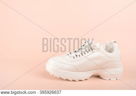 One White Sneaker Isolated On Pastel Background. Clean New Trendy Sneaker On Pink Background. Sport
