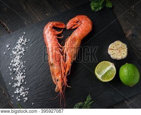 Two Large Langoustines With Lime, Salt, Garlic And Herbs On A Black Plate. Seafood Healthy.
