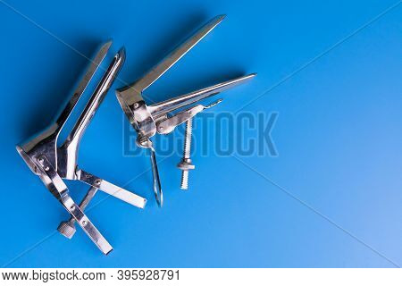 Two Different Gynecological Mirrors On A Light Blue Background. Copy Space Gynecological Examination