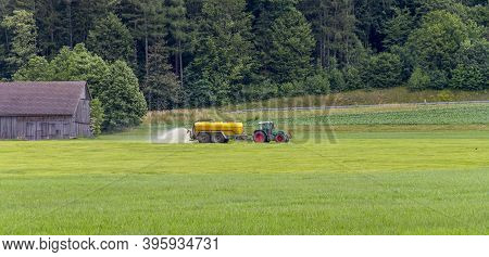 Rural Scenery Including A Tractor Spreading Liquid Manure At Summer Time