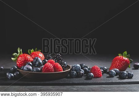 Assorted Berries On Slate Plate On Dark Background With Copy Space.