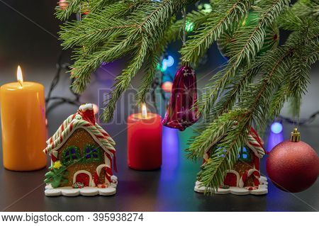 Christmas Candle, Gingerbread House And Festive Decor On A Dark Background. Holiday Concept For Chri