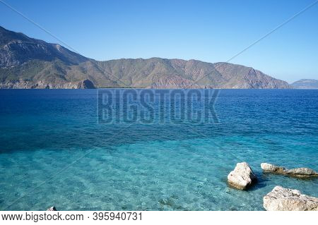 Coast Landscape With Mountains On Background. Crystal Blue Sea Waves On A Sunny Day. Beautiful Water