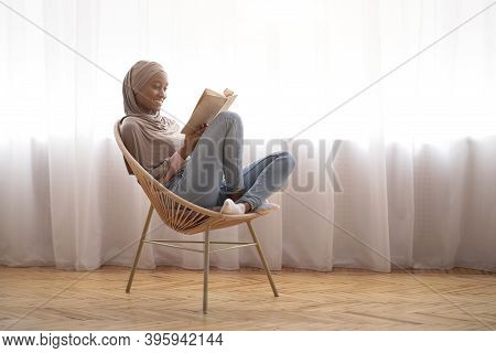 Black Muslim Woman In Traditional Headscarf Relaxing In Comfy Armchair With Book At Home, Empty Spac
