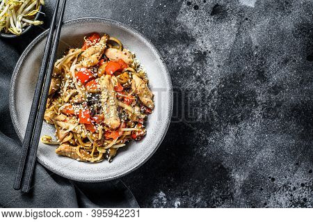Chicken Stir-fry. Wok Udon Noodles. Traditional Asian Food. Black Background. Top View. Copy Space