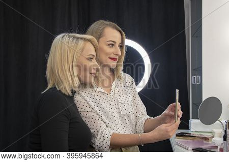 Portrait Of Two Female Friends Who Take Photos Of Themselves And Their Hairstyles In A Hair Salon.