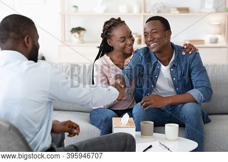Grateful Black Spouses Shaking Hands With Counselor After Successful Marital Therapy, Happy African