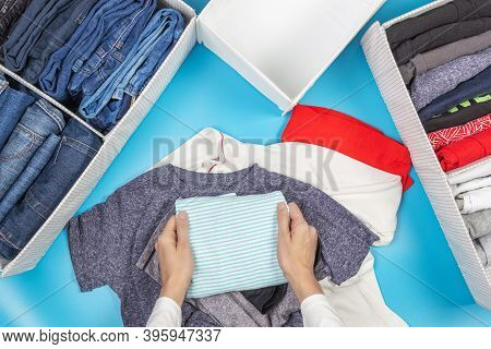Woman Hands Folds And Puts Clothes To Baskets. Vertical Storage Of Clothing, Tidying Up, Room Cleani