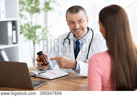Medicine And Health Care Concept. Experienced Doctor Showing Female Patient Bottle With Pills, Point