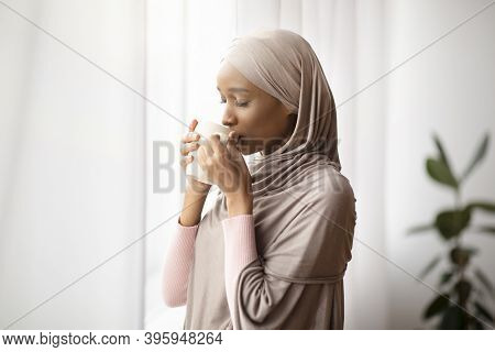 Young African American Woman In Hijab Having Lazy Morning With Aromatic Coffee At Home, Drinking Hot