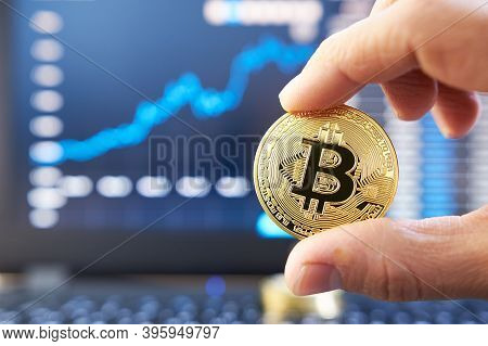 Male Hand Showing Gold Bitcoin. Laptop Keyboard With Basic Candlestick Green Red Graph Price In Back
