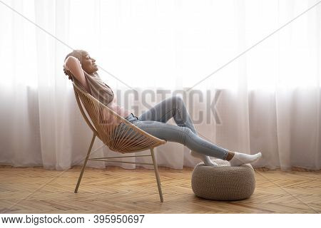 Side View Of Happy Muslim Woman In Hijab Relaxing In Comfortable Armchair, Resting Her Feet On Knitt