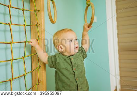 Small Kid Trying To Reach Wooden Gymnastic Rings