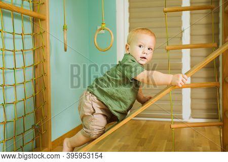 Little Boy Climbing On Indoor Wooden Slide