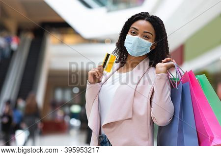 Pandemic Shopping. African American Woman In Medical Mask Posing With Shopper Bags And Credit Card I