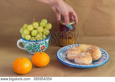 Woman's Hand Catching A Pot Of Honey Surrounded By Some Traditional Spanish Cakes, Grapes, Tangerine