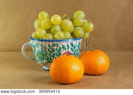 Bunch Of Grapes Presented In A Traditional Hand-painted Ceramic Vase Next To Some Tangerines