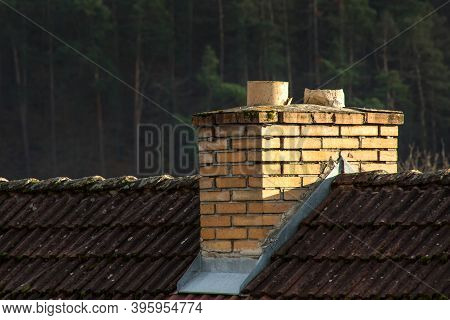 Old Brick Chimney On Roof. Ecological Concept. Coal Heating.