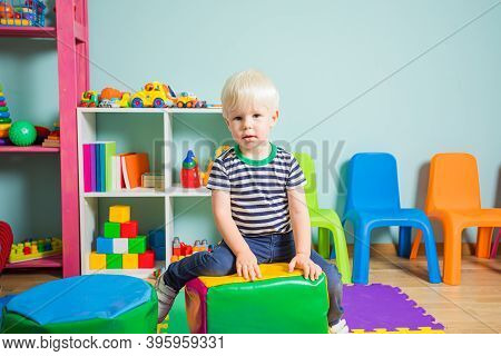 The Toddler Boy Is Sitting On A Pouf In The Kindergarten