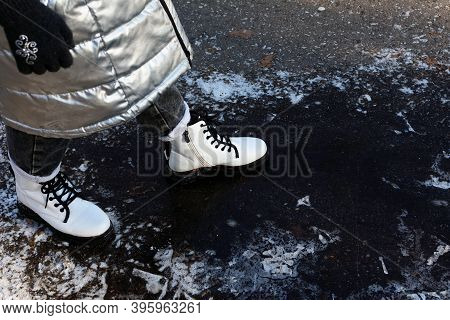 Female Legs In White Boots Carefully Walking On Slippery Road With Frozen Puddle Covered With Ice. D