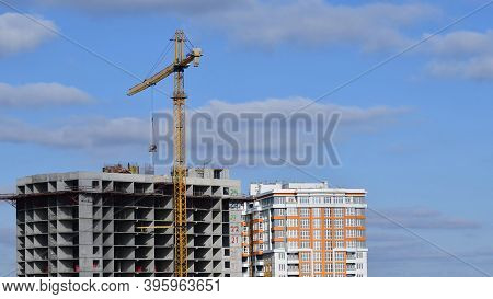 Construction Site At Rooftop Of Unfinished Skyscraper With Big Tower Crane Lifting Up Construction M
