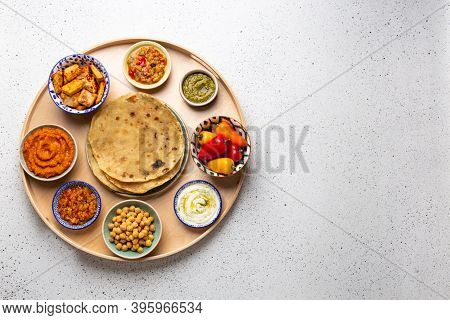 Indian Thali - Selection Of Various Dishes Served On Round Wooden Platter, White Table. Assorted Ind