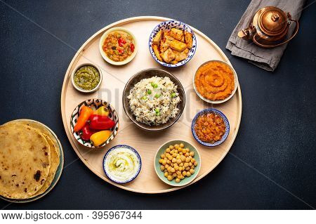 Indian Thali - Selection Of Various Dishes Served On Round Wooden Platter. Assorted Indian Vegetaria