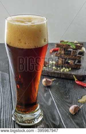 Glass Of Dark Beer And Crunchy Rye Toast On Dark Wooden Background