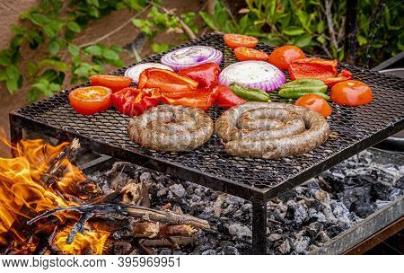 Barbecue On Fire With Handmade Sausage And Vegetables