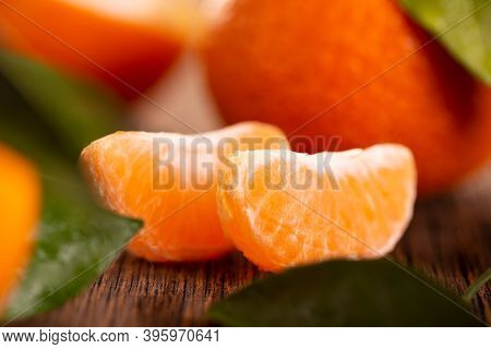 Tangerine Slices Close Up. Ripe Tangerine On A Wooden Table. Two Slices Of Juicy Tangerine.