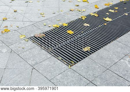Grating Of The Drainage Storm System On The Pedestrian Park Sidewalk Made Of Gray Stone Granite Tile