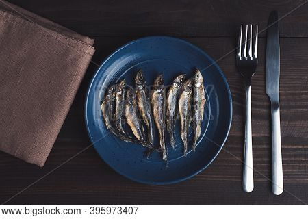 Dried Smelt Fishes On Plate With Fork And Knife, High Angle View, Wooden Background. Concept Of Diet