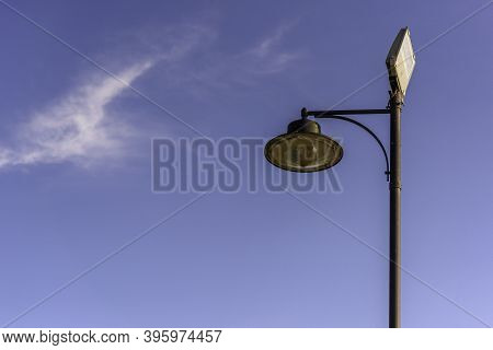Street Lamp With Two Types Of Lamps, Vintage And Modern Spotlight. Blue Sky Background With Copy Spa