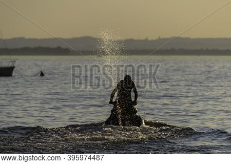 Back View Of Man Riding A Fast Water Scooter With Splashing Water. Through Some Low Waves At Sunset