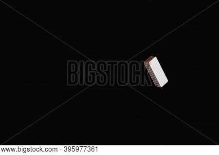 One Levitating Chocolate Wafer On A Black Background
