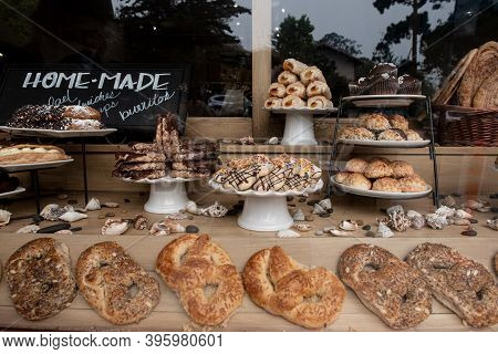 Carmel, Ca, Usa, 09 September 2020. Pastries On Display In A Bakery Seen Through The Glass  On A Str
