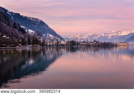Zell Am See In Winter Evening. View Of Lake Zell, Town, Mountains And Snow With Reflections In Water