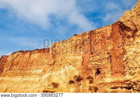 Rocks On The Shore Of Benagil Beach In Portugal. Sandy Orange Embankment Hill Against Blue Sky