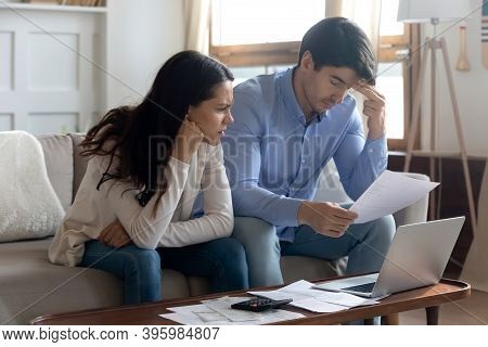 Concerned Young Married Couple Studying Bank Letters Informing About Debt