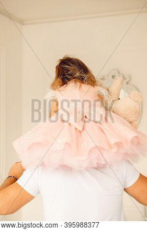 Little Girl In A Beautiful Dress Sits On Daddy's Neck