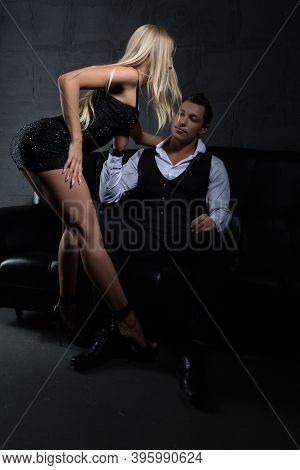 A Sexy Blonde Woman With A Beautiful Figure Dances A Striptease To A Brutal Businessman Sitting On T